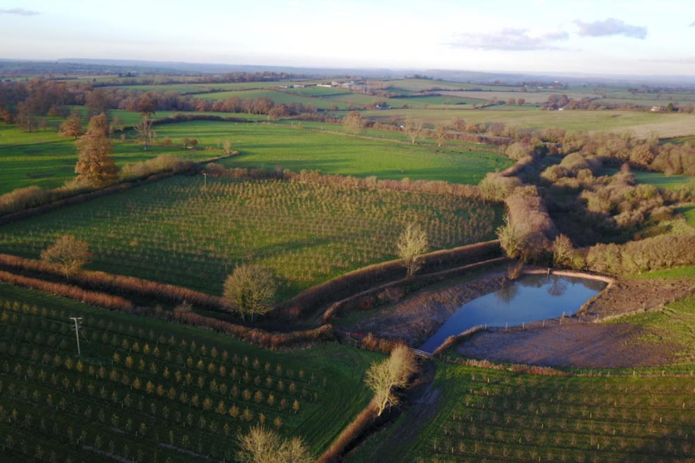 An Aerial Photograph Of A Leaky Pond In Odcombe, West Of Yeovil. The Pond Has Been De-silted And Improved With A New Water Management Pipe Structure At The Pond's Outlet. The Work Was Funded By Somerset Rivers Authority To Help Slow The Flow Of Water Down To Wellhams Brook, In The Catchment Of The River Parrett, As Part Of Somerset's Award-winning Hills To Levels Project.