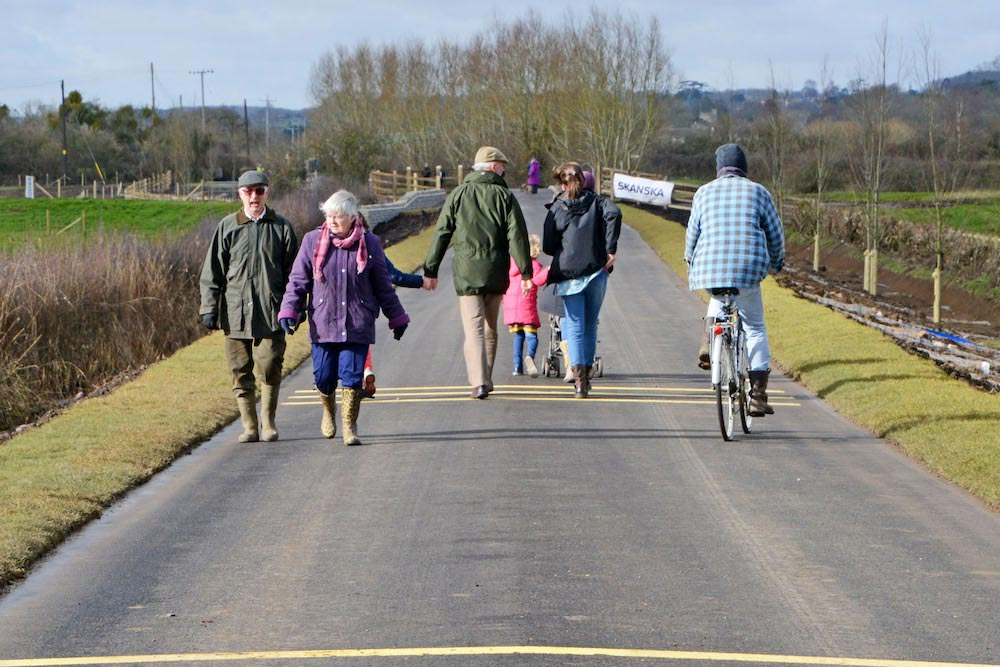 Local Residents Walk Along Muchelney Raised Road With Cyclist.