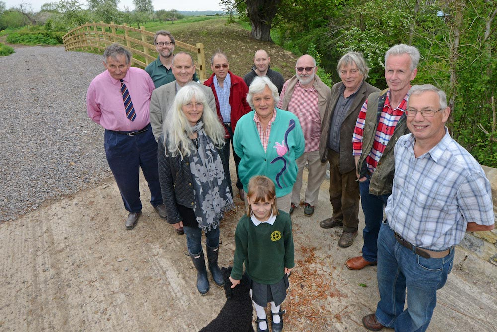 Small gathering of Thorney residents and official representatives near completed Thorney ring bank.