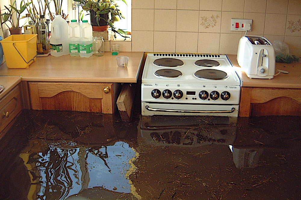 Kitchen Units And A White Cooker Nearly Submerged In Dark Brown Flood Water In February 2014.