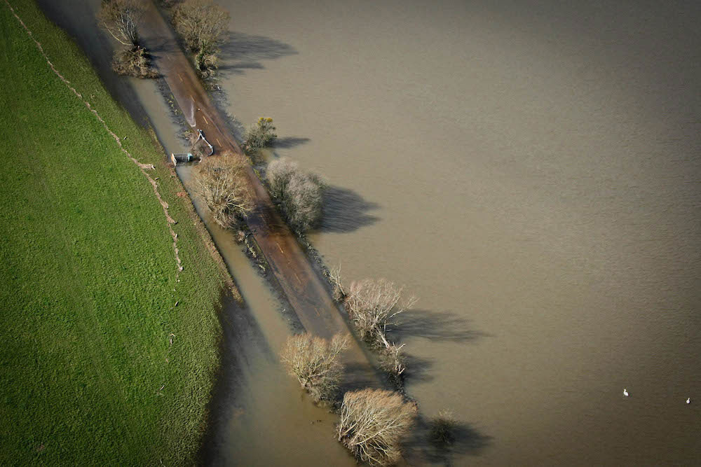 Aerial View Of Flooded Road And Fields With Two Swans On The Water In Somerset February 2014