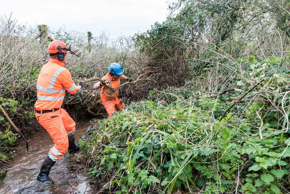 Two Contractors Clearing A Badly Overgrown Stream At Carhampton For Somerset Rivers Authority.