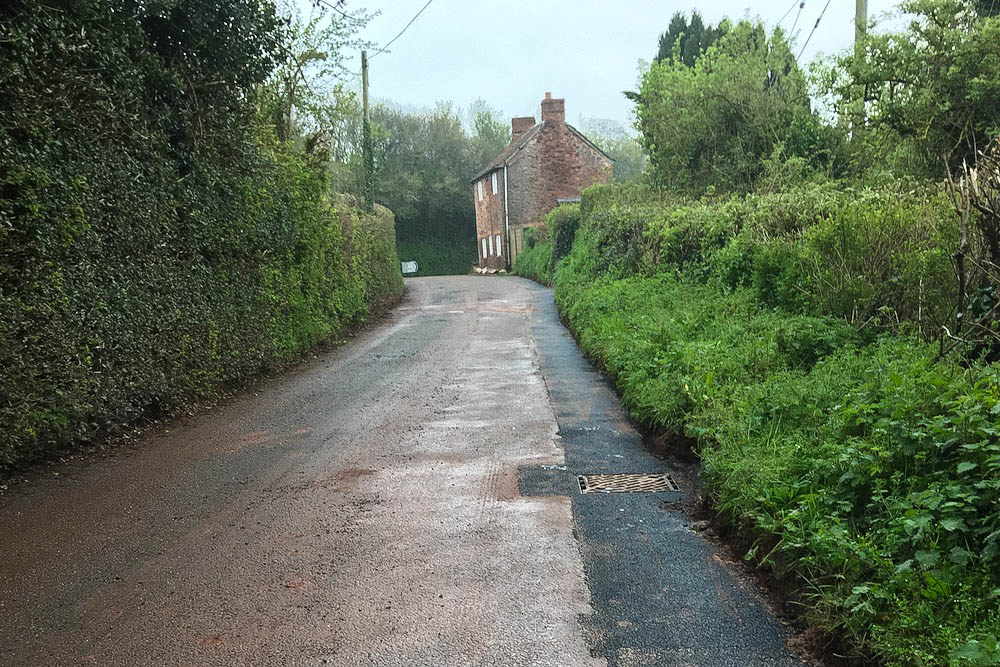 Monksilver B3188 main road reopened with fresh tarmac along edge where drainage improvements made for Somerset Rivers Authority in April 2019