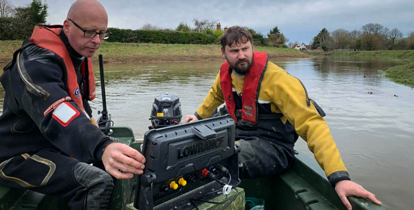 Two scientists on boat on River Parrett, one looking at a computer screen, for an investigation into fish movements and behaviours using acoustic technologies.