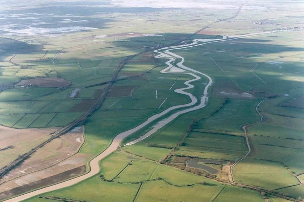 Aerial view of the River Parrett's intersection with the River Sowy at Monk's Leaze Clyse near Aller and both rivers then snaking away across the Somerset Levels.