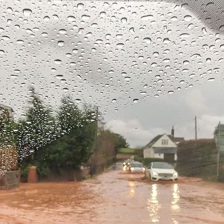Cars moving cautiously along flooded A39 at Carhampton Cross in December 2019.