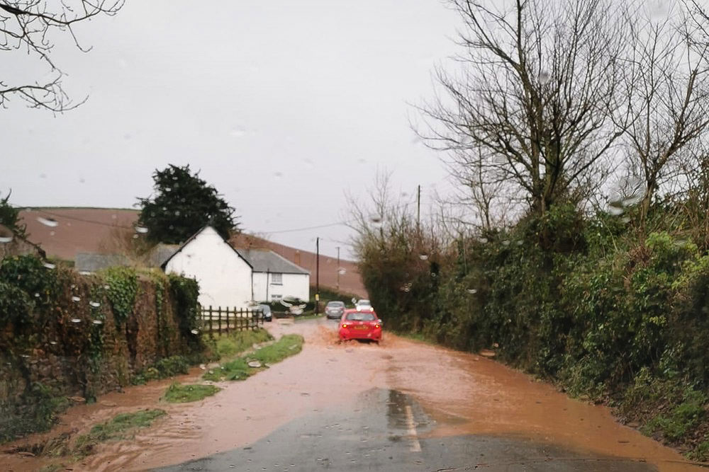 Flooding along Eastbury Road in Carhampton with cars driving down the centre of the road.