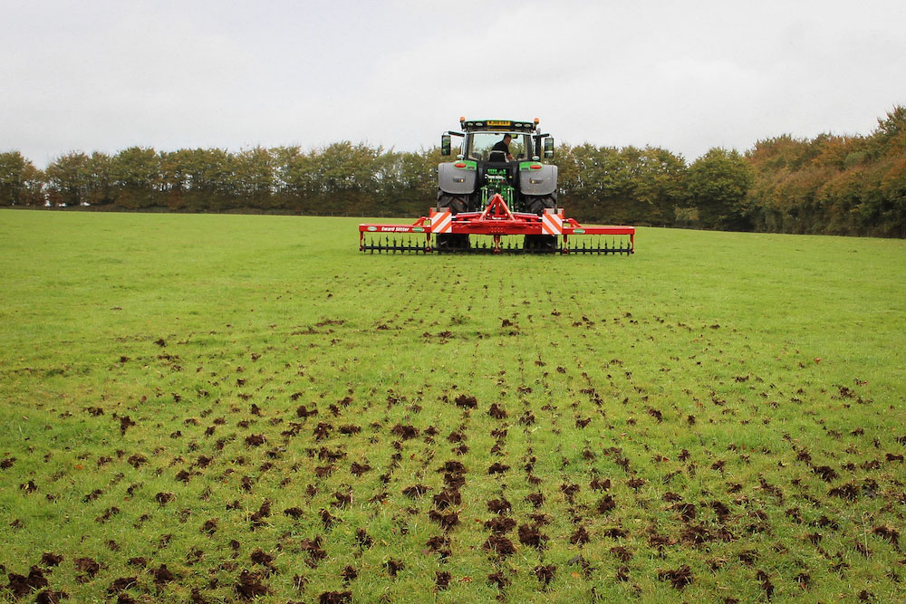 Tractor and Sward Slitter in action on field in Exmoor in Somerset with grassland showing results of efforts to aerate soil and improve infiltration of water.