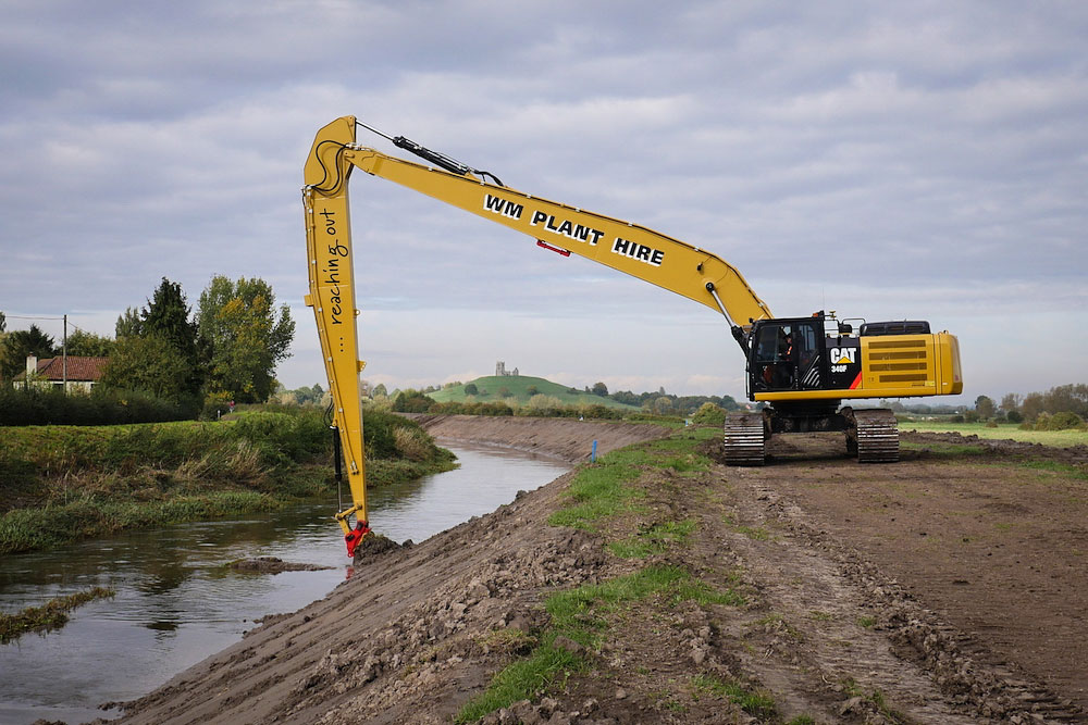 A long-reach excavator dredging the River Parrett with Burrow Mump in the distance