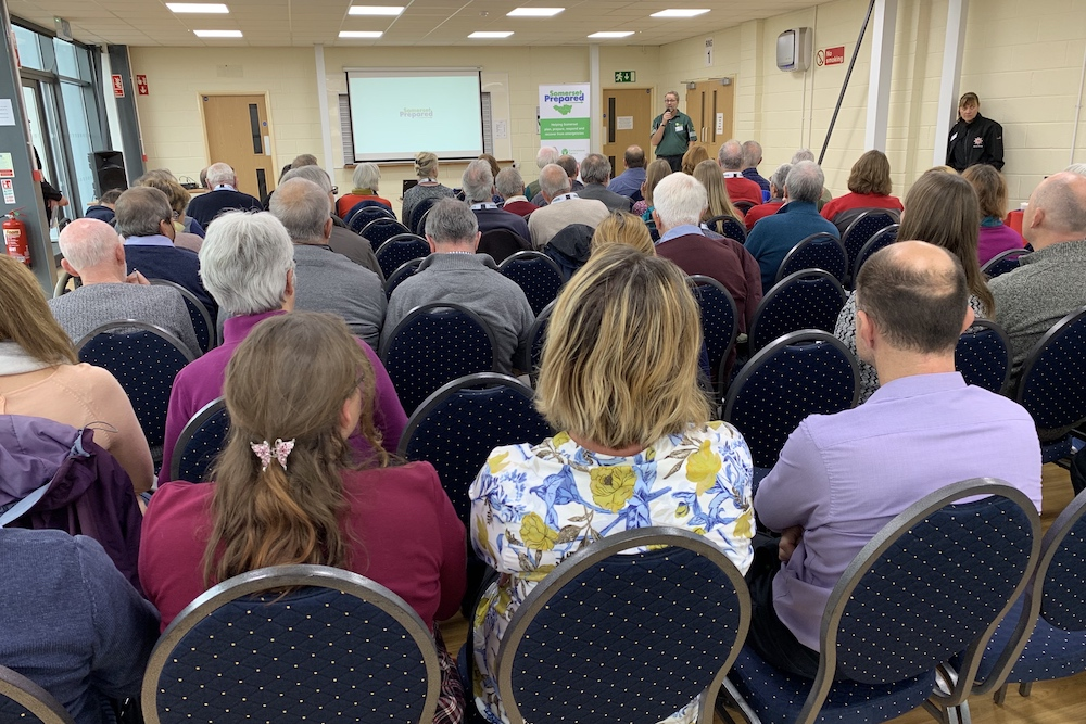 View from back of large room of audience listening to speaker John Rowlands of the Environment Agency, with screen saying Somerset Prepared.
