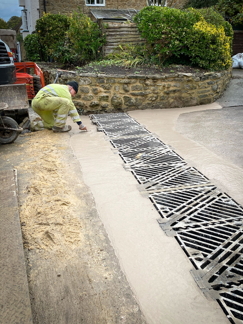 Contractor smoothing cement around new silt trap now covered with series of grilles in Bonnings Lane in Barrington.