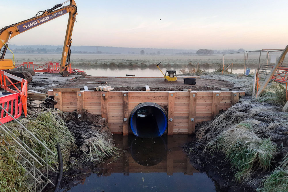 A new culvert set in a new timber headwall looking from Othery Rhyne across to King's Sedgemoor Drain and the Somerset Levels beyond on a frosty morning, with construction equipment and fencing to both sides.
