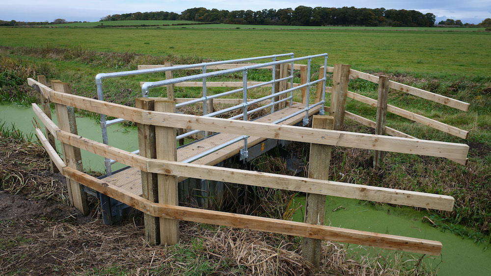 A water level control structure with new walkway and fencing, looking out over Westmoor towards distant fields and trees.