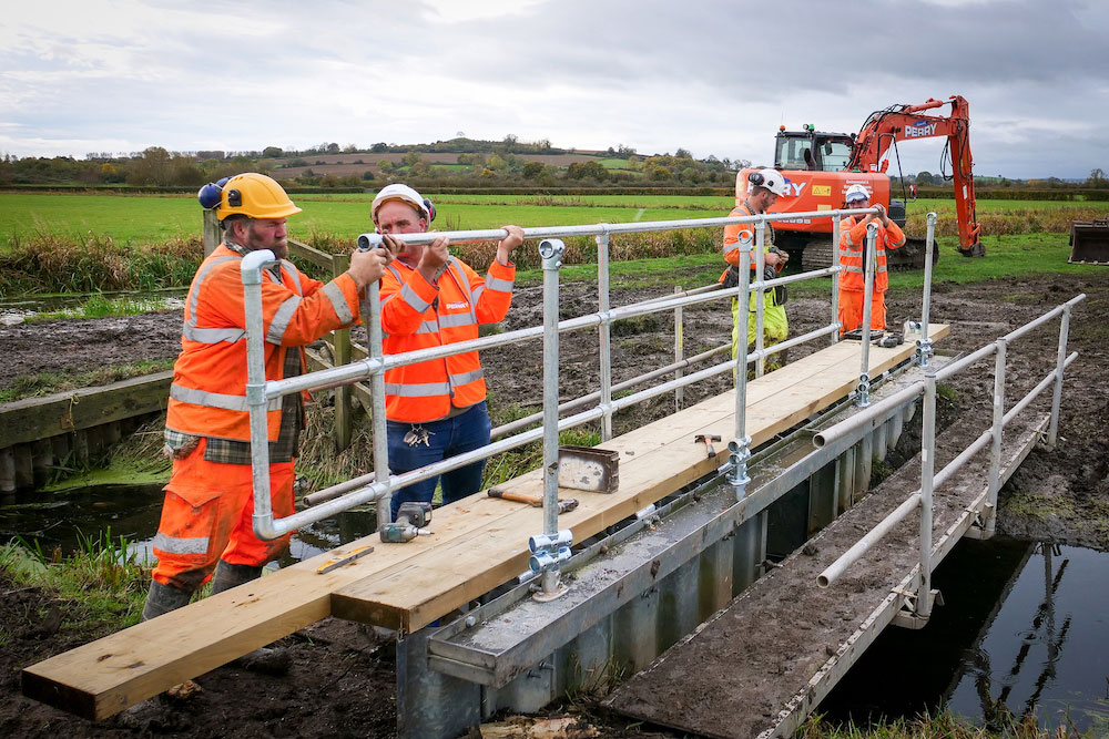Four Men From Contractors Bernard Perry Fitting The Railings Of A New Walkway On A Westmoor Water Level Control Structure For Somerset Rivers Authority.