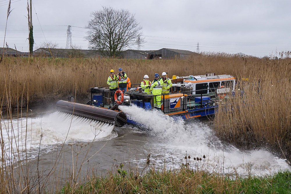 Observers From The Environment Agency And Parrett Internal Drainage Board, On Board Van Oord's Water Injection Dredging Vessel Borr, See Water Being Jetted Out From Borr's Water Injection Bars, Raised For Demonstration Purposes Above The Surface Of The River Parrett Near Moorland.