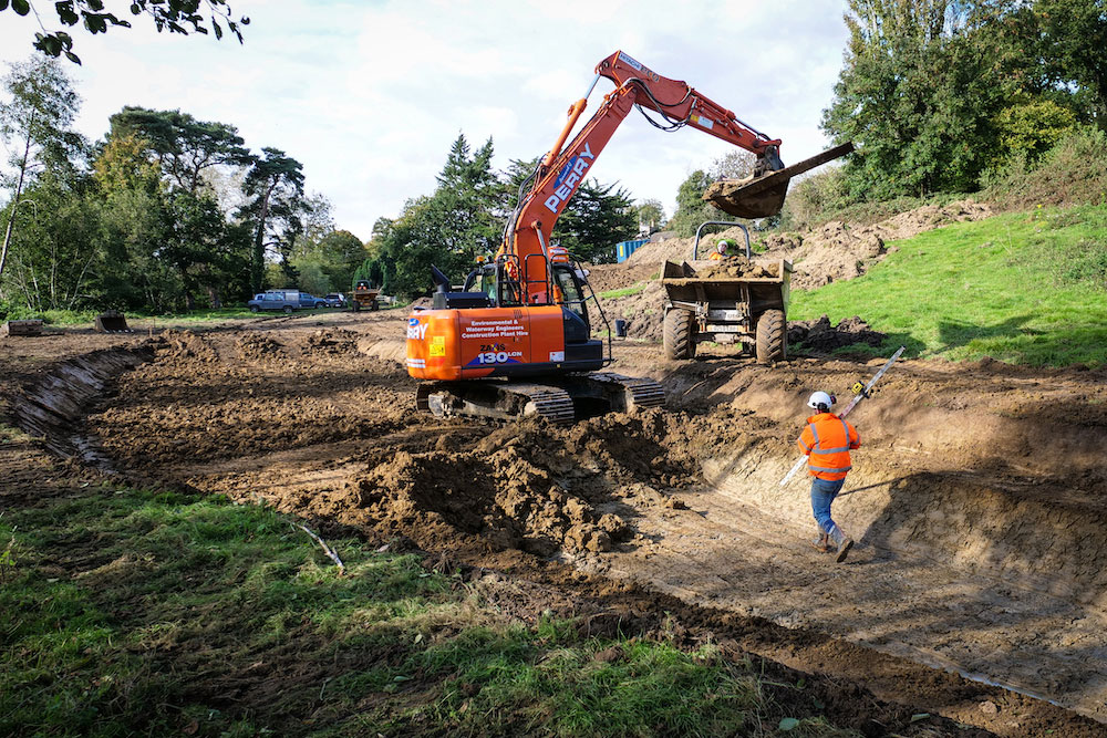 A Tracked Excavator Deposits Soil In A Front-loading Dumper In A Field Near Montacute House In Somerset.