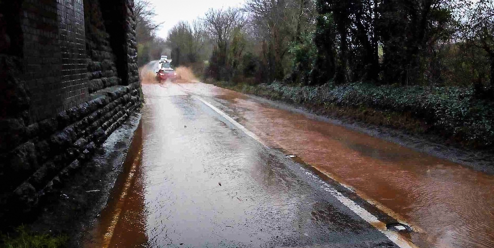 A car in the centre of the A358 near Combe Florey splashing through soil-coloured flood water , with other cars queued up waiting to go through.