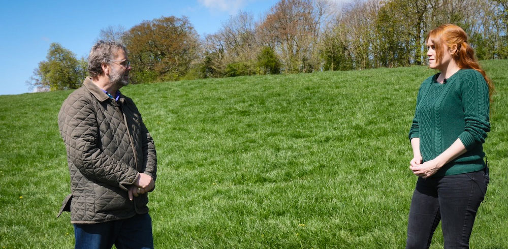 John Rowlands and Shelly Easton stood socially-distanced on a grassy hillside near Wedmore with trees at the top.