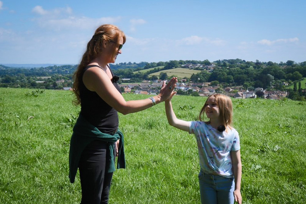 Shelly Easton And Iona High-five Each Other On Lascott Hill With Wedmore And Surrounding Countryside Stretching Out Behind Them Into The Distance.